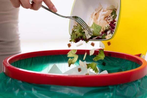 donna che getta verdure nel cestino