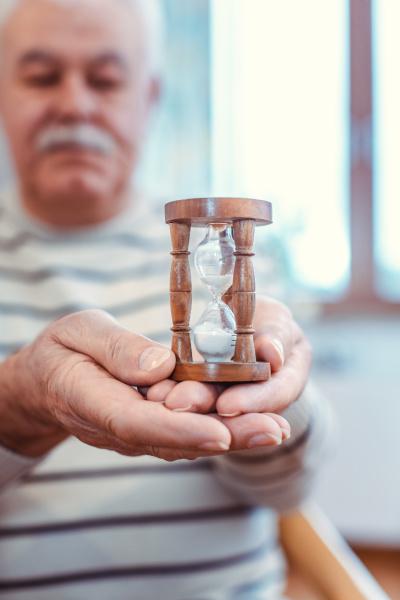 uomo anziano in possesso di clessidra
