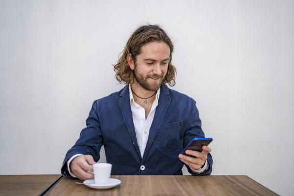 sorridente belluomo daffari usando lo smartphone