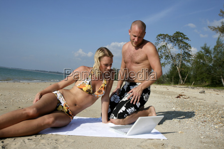 couple with laptop at the beach