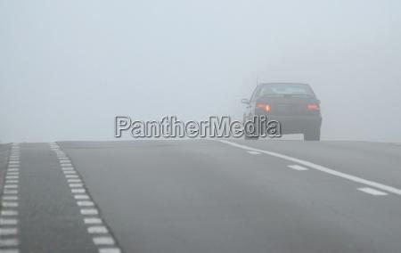 auto che scompare attraverso la nebbia