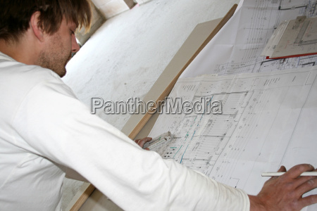 worker looks at construction drawing