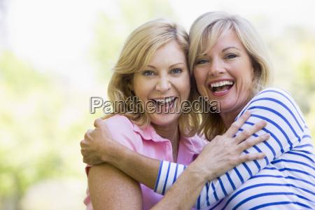due donne allaperto abbracciando e sorridendo