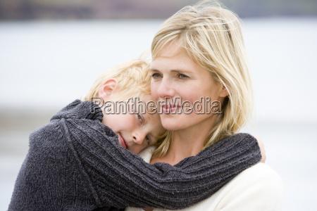 madre che tiene figlio in spiaggia