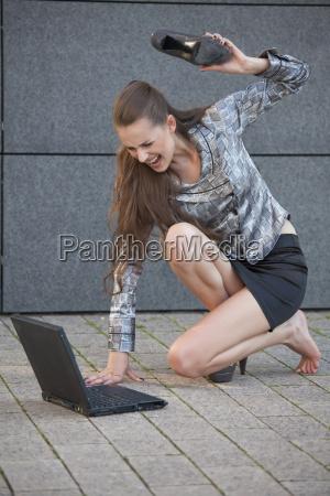 donna batte laptop con scarpa
