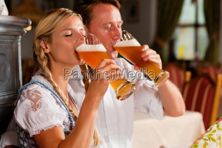 coppia in costume beve birra bianca