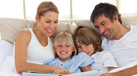 famiglia gioiosa leggendo un libro sul