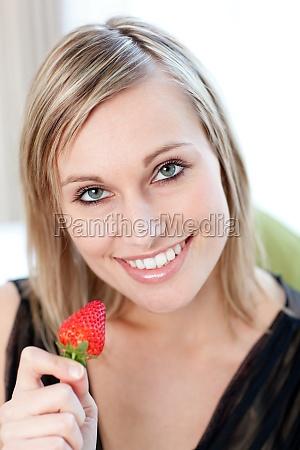 donna affascinante che mangia una fragola