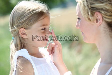 madre e figlia mettendo protezione solare