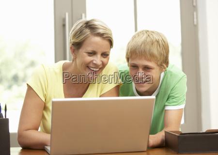madre e figlio adolescente con laptop