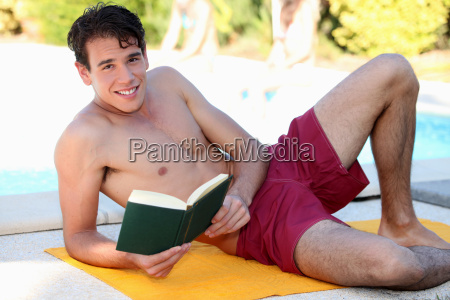 young man reading book at the