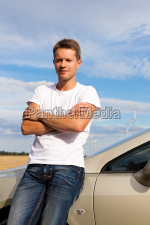 man leaning on his car