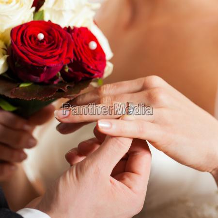 sposi con bouquet da sposa e