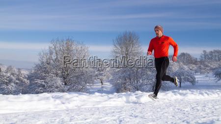 jogger nel paesaggio invernale innevato