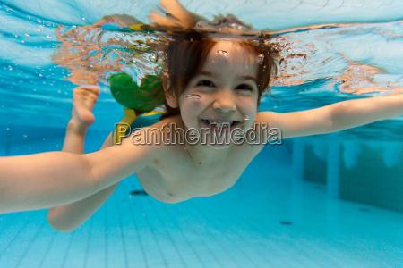 la ragazza sorride nuota sotto lacqua
