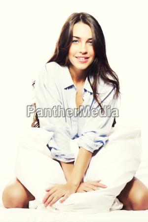 beautiful brunette woman kneeling in bed