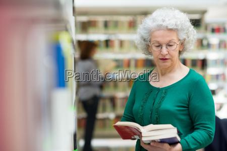 donna anziana leggere e scegliendo libro
