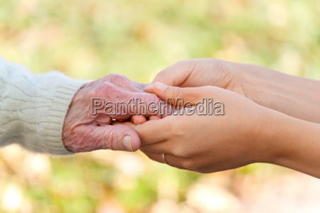 tenendosi per mano senior e giovani