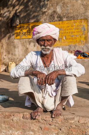 un vecchio uomo indiano seduto con