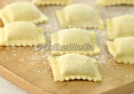 uncooked ravioli on a cutting board
