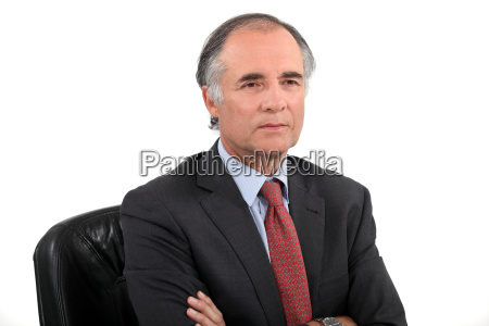 senior businessman sat with his arms