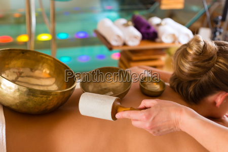 woman at wellness and sound bowls