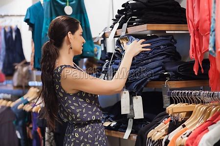 donna accatastamento di jeans su scaffale