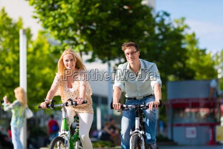 coppia in citta cavalca bici nel