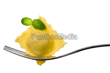 ravioli pasta parcel and basil garnish