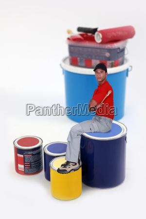 pittore seduto su lattina di vernice
