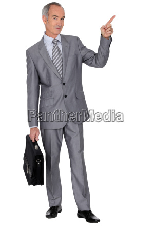 senior man in a suit pointing