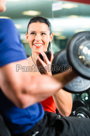 personal trainer in gym and dumbbell