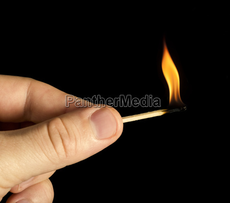 hand holding burning match stick