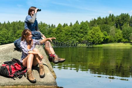 escursionisti adolescenti birdwatching sul lago