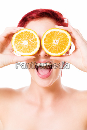 enthusiastic young woman holds oranges in