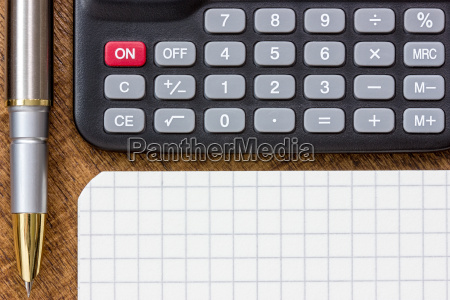 calculator pen and notepad on the