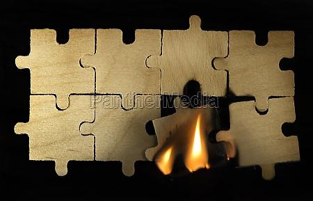 burning wooden puzzle on dark background