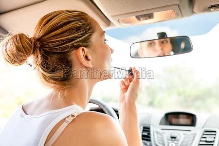 trucco giovane donna nello specchietto retrovisore
