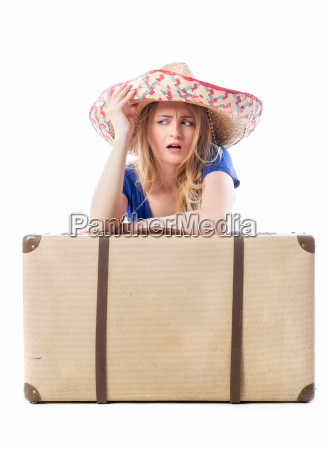 blond girl sitting behind a suitcase