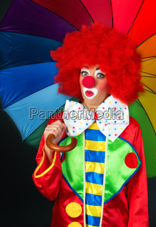 astonished clown with umbrella