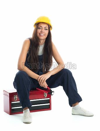 female apprentice sitting on toolbox