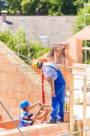 craftsmen control walls on building site