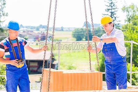 crane operator provides pallet bricks on