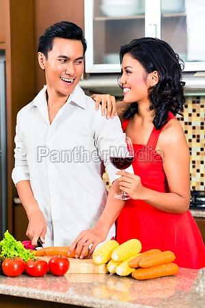 coppia asiatica preparando cibo in cucina