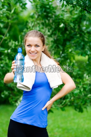 smiling woman showing water bottle after