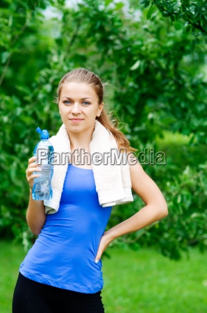 smiling woman with water bottle after