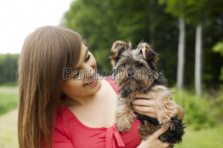 smiling woman holding cute puppy