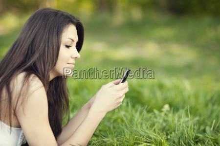 young woman texting on meadow