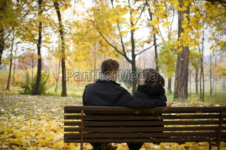young couple sitting on bench in