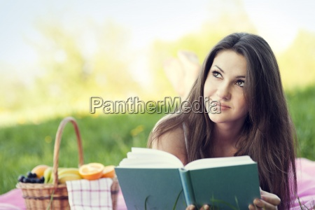 young woman reading on meadow